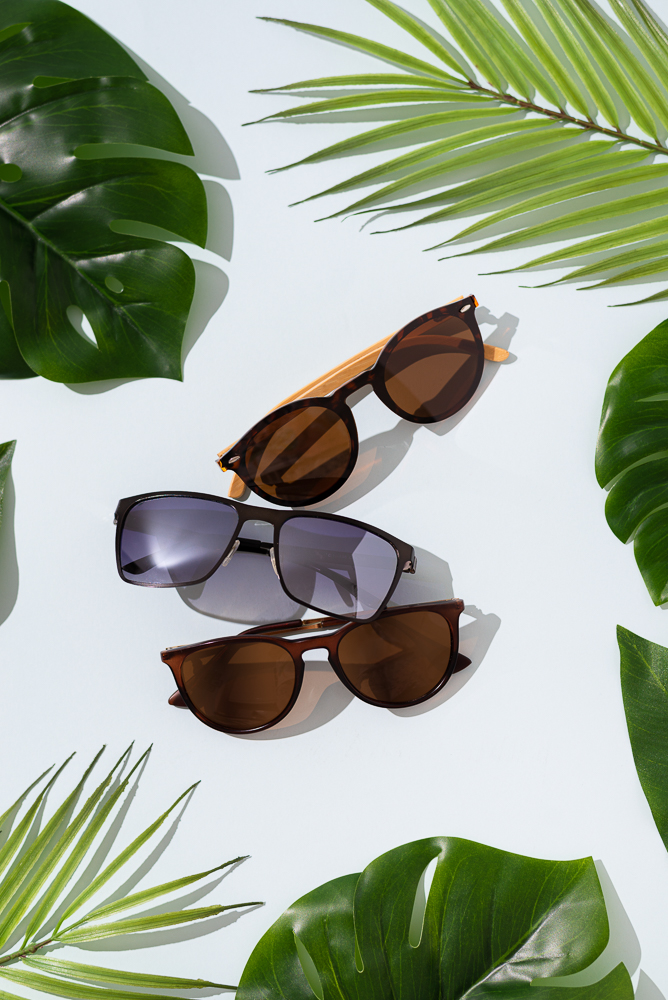 Trendy sunglasses of different design on blue background with tropical monstera and palm leaves. Sunglasses sale banner concept. Fashion summer accessories. Top view