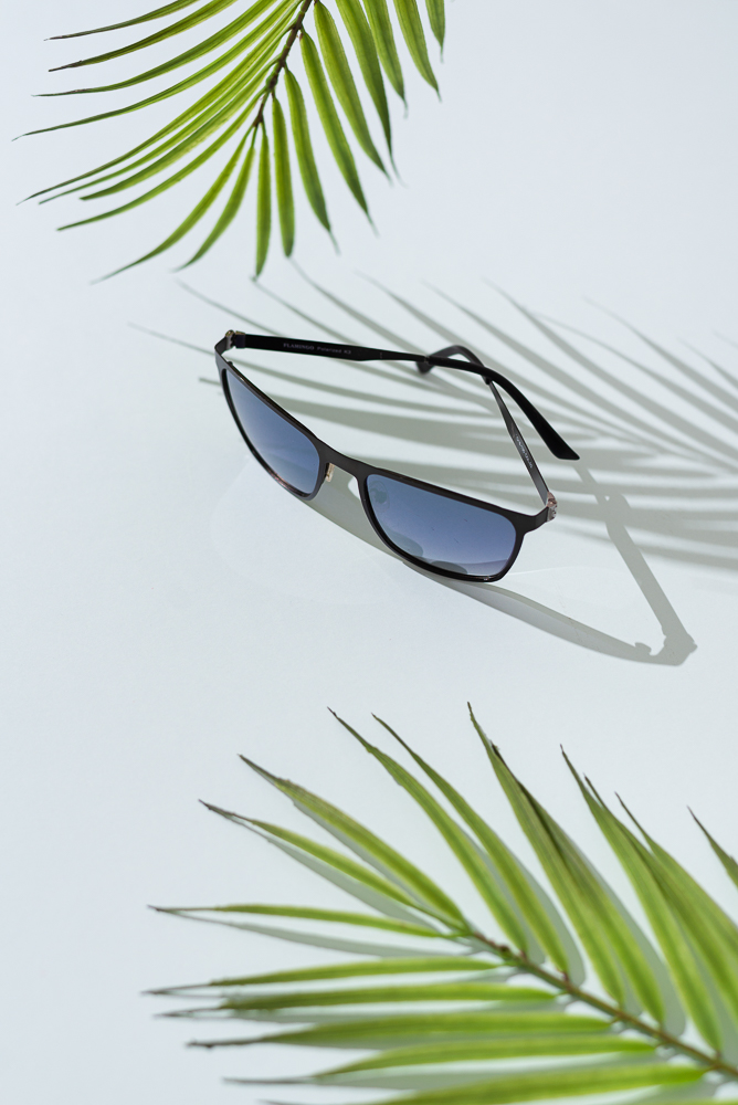 Sunglasses sale concept. Trendy sunglasses on blue background with tropical palm leaves and shadows. Trendy Fashion summer accessories. Side view. Vacation, summer holidays, travel concept