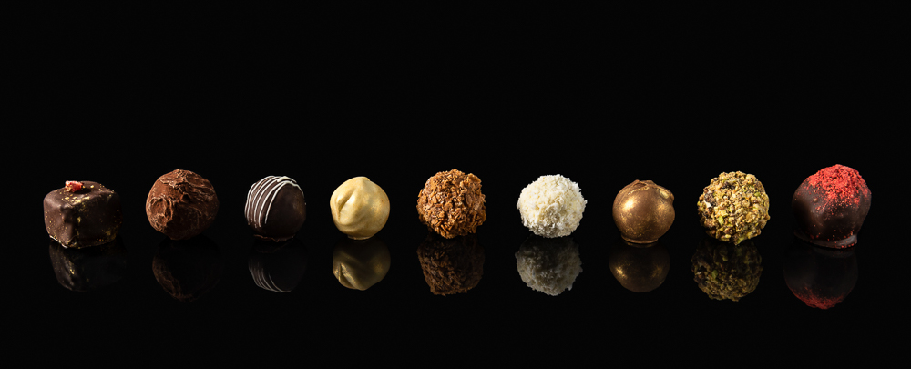 Set of fine chocolate candies White, dark and milk chocolate on black background with reflection