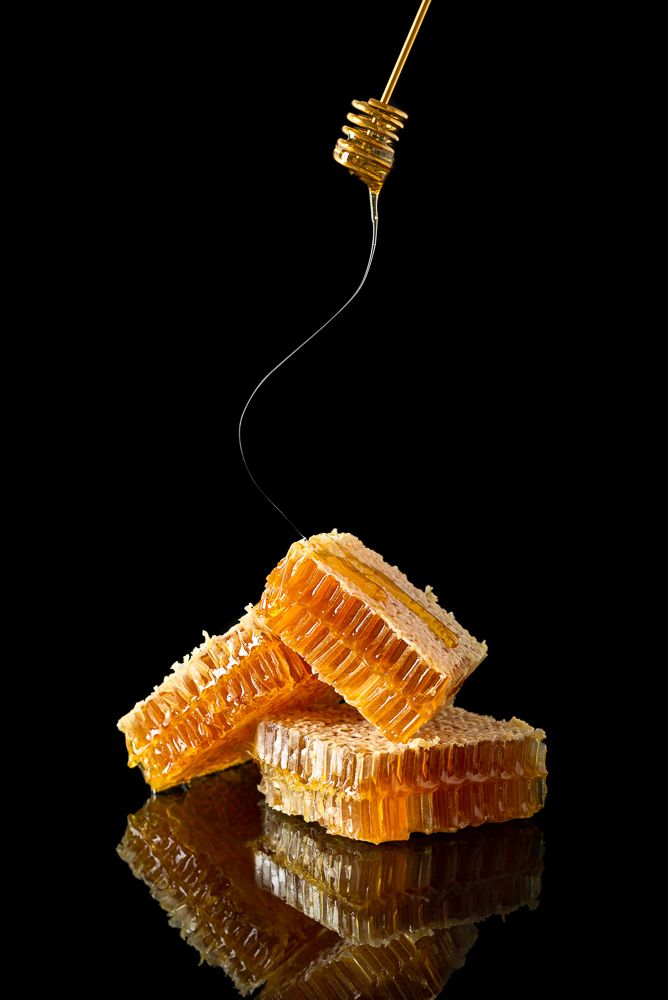 Sweet honeycomb and golden dipper with dripping honey on black background with reflection, bee products by organic natural food ingredients. Beekeeping advertisement, banner
